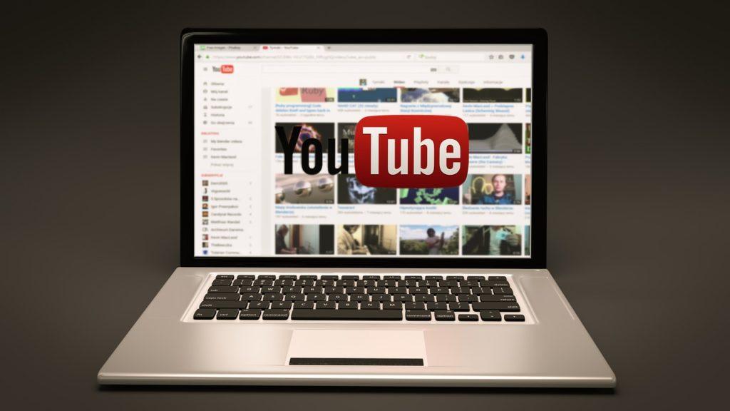 Laptop mit Startseite von YouTube vor dunklem Hintergrund